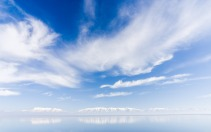 Salt Lake, in Utah, reflects the bold, blue sky. Birds can be seen swimming in the distance.